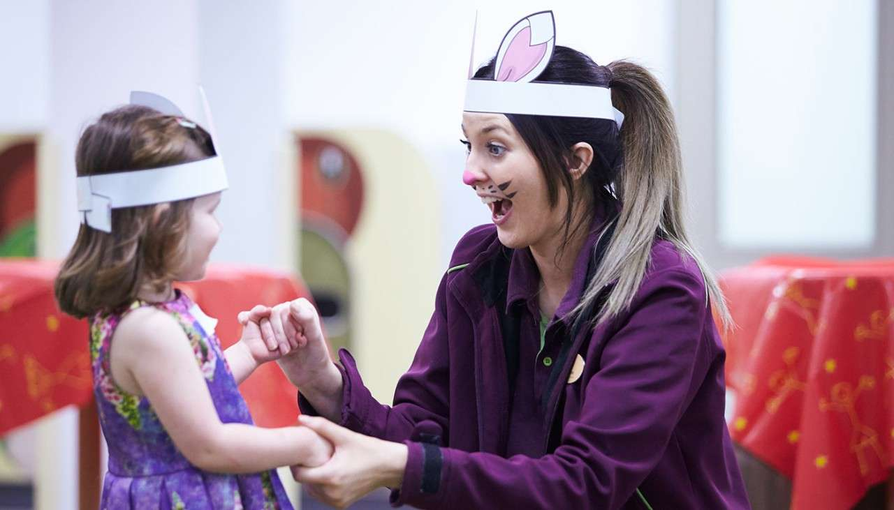 Girl wearing bunny ears in an activity at the Activity Den