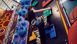 Girl climbing up a colourful climbing wall on Indoor Climbing Adventure