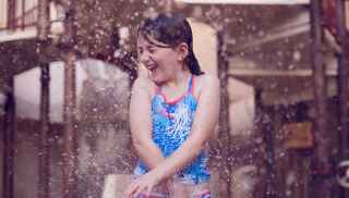 Girl splashing in water play area at the Subtropical Swimming Paradise