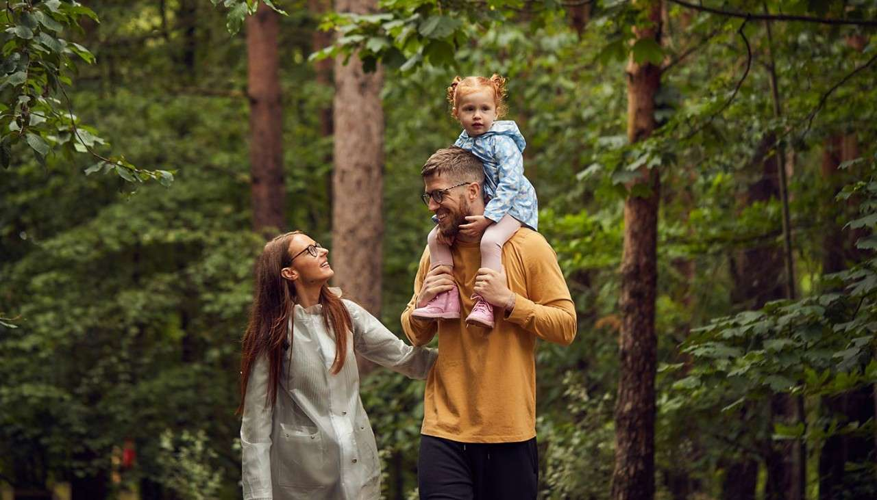 Young boy wearing a rain coat and wellies splashing in a puddle