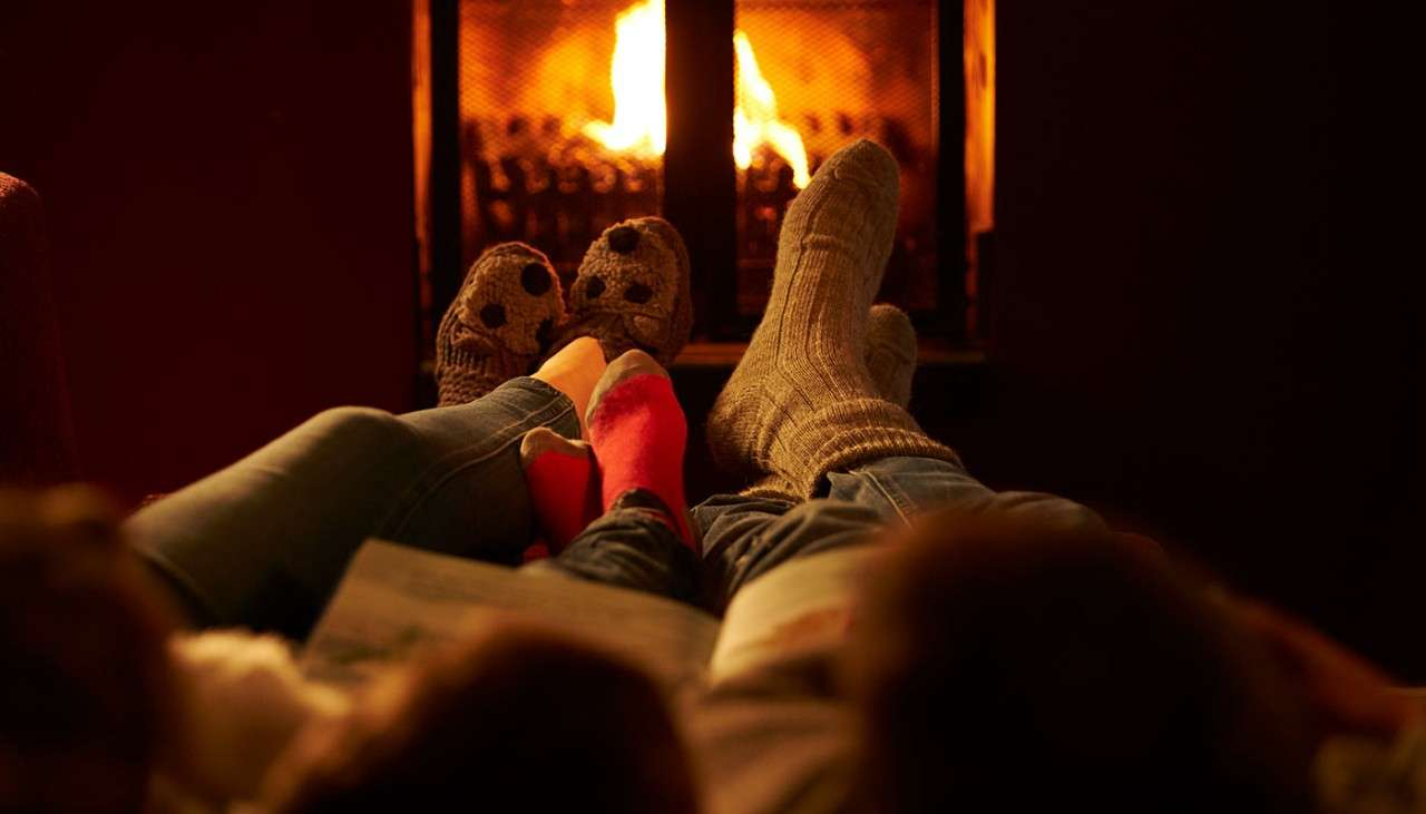 Family warming up by log fire