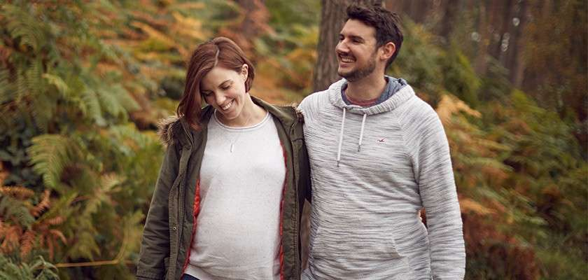 Pregnant couple walking through the forest