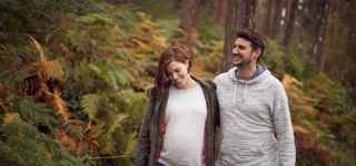 Pregnant couple walking through forest