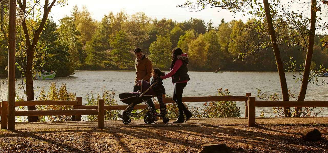 Parents with pram walking around Center Parcs lake in the autumn