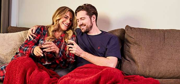 Couple sat on a sofa in their lodge wrapped in a blanket with glasses of red wine