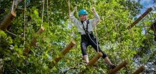 A girl doing our aerial rope course in the trees - Aerial Adventure