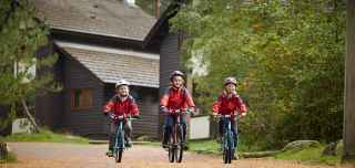 Three boys on cycles through Center Parcs with lodges behind them