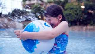 Girl playing with an inflatable ball in the Subtropical Swimming Paradise