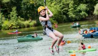 Girl in harness and helmet on a zip wire over the lake at Elveden Forest