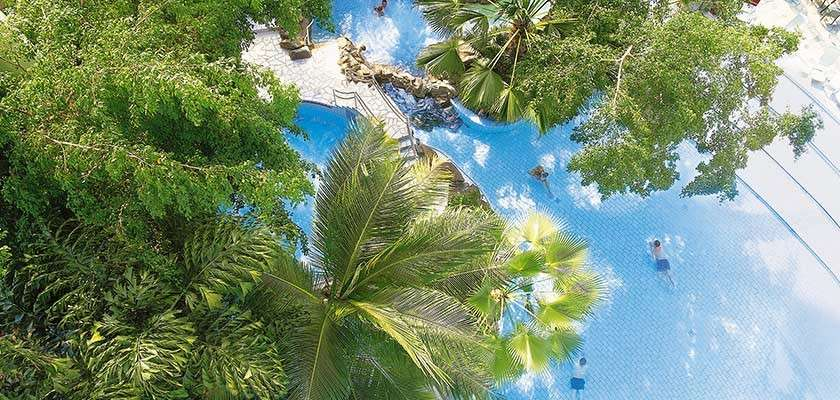 Interior of a lodge at Center Parcs showing open plan living with kitchen, corner sofa, and dining table