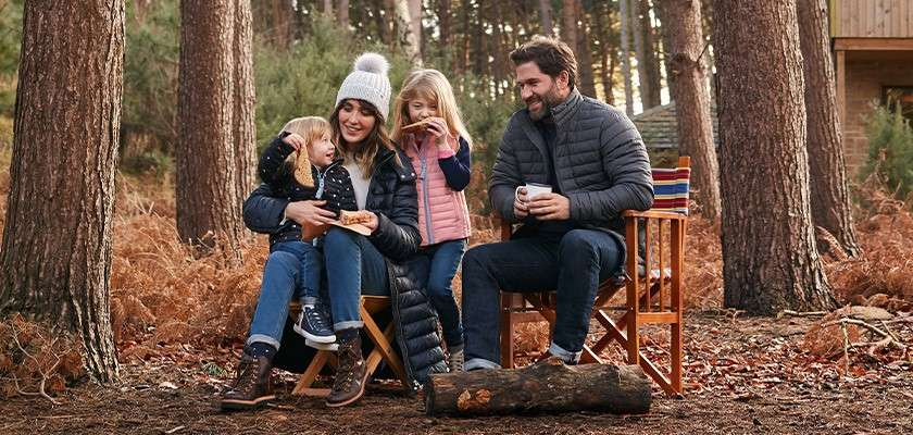 Family in the forest wearing Joules clothing