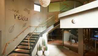Text: 'And relax' Stair case leading to new spa extension showcasing new experience rooms.