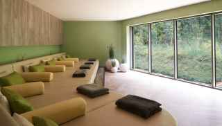 Padded bed relax area looking out onto a secluded woodland area.